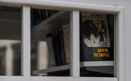 A picture of a group of books sitting on a shelf inside a phone booth.