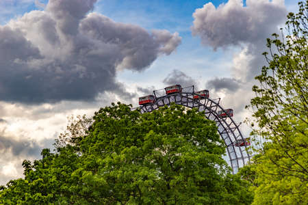A picture of the iconic Prater Ferris Wheel as seen from the nearby vegetation.