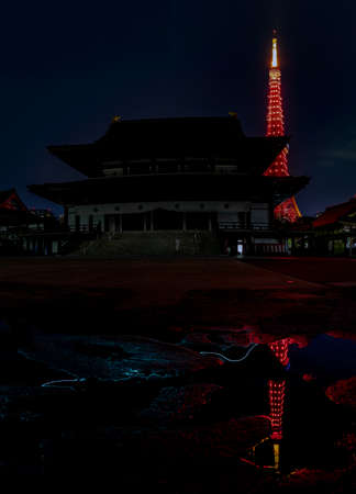 A picture of the Tokyo Tower as seen from the Zojoji Temple, at night.