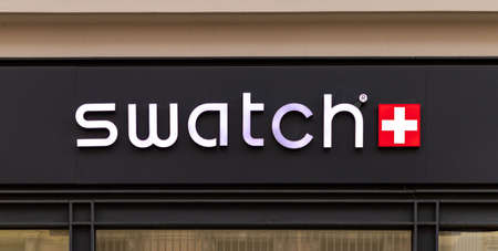 A picture of the Swatch logo on display above a store.