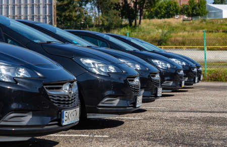 A picture of a row of black Opel cars on a parking lot. Editorial