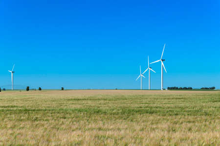 Wind turbine lined up in a field in the countryside. Structure that works with the wind to generate electricity. Renewable energy concept.
