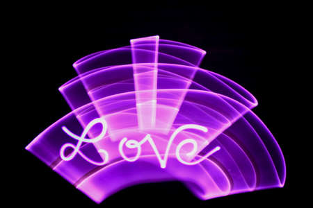 Word love written with a led lamp during a lightpainting session at night. Abstract curved shape drawn with a light saber.