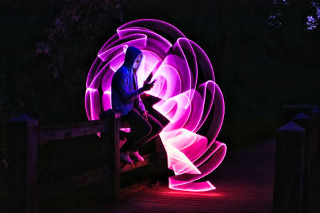 Man sitting on a bridge with his smartphone in his hand. Violet light effect with a light saber in lightpainting. People using technology.