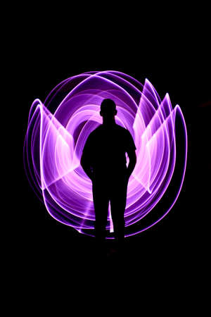 Silhouette of a man standing from the front. Curved abstract shapes made of violet light saber in background. Lightpainting session in long exposure at night.