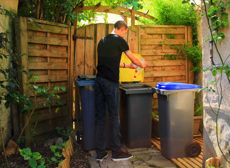 Person making a selective sorting of waste. Man putting plastic bottles in a yellow bin for recycling.