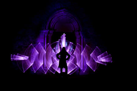 Lightpainting session at night. Silhouette of a woman in front of an arch carved in stone. Curved abstract shape made with a light saber violet. Leds light effect. Background for wallpaper.