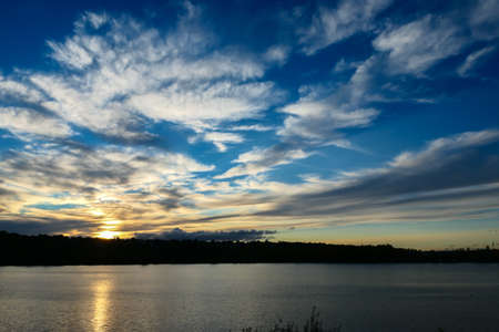 Amazing sunset over the water. Beautiful landscape with a lake and dramatic sky with cumulus clouds on the horizon.