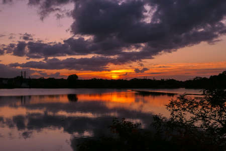 Amazing sunrise in rural scene. Symmetry of the sky in a lake at sunset. Clouds reflecting on the water. Quiet relaxing scene with a beautiful colorful cumulonimbus. 版權商用圖片