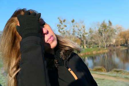 Portrait of a blonde woman in winter by a lake, passing hand in hair. 版權商用圖片
