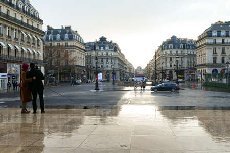 Paris, France. January 17. 2021. View in perspective with reflection in puddle of Haussmann-style buildings. Couple using technology in the street with smartphone.