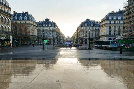 Paris, France. January 17. 2021. View in perspective with reflection in puddle of Haussmann-style buildings. RATP Public Transport bus.