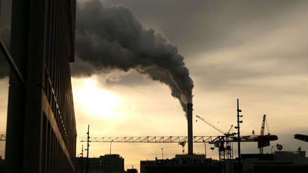 Paris, France. January 24. 2021. Industrial chimney of a smoking factory. Polluting smoke rising in the sky. Environmental pollution concept.