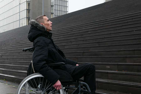 Concept of disabled person. Man in a wheelchair outside in the street in front of stairs. Background blurred voluntarily.