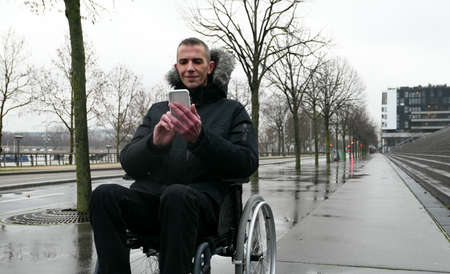 Concept of disabled person. Man in a wheelchair outside in the street. People using technology with smartphone. Background blurred voluntarily.