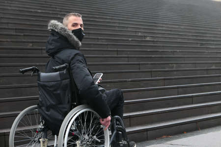 Concept of disabled person. Man in a wheelchair in front of stair, outside in the street. 版權商用圖片