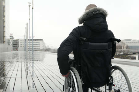 Concept of disabled person. Man in a wheelchair outside in the street. Background blurred voluntarily.