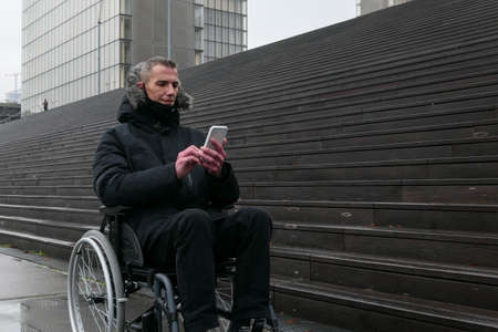 Concept of disabled person. Man in a wheelchair outside in the street in front of stairs. People using technology with smartphone. Background blurred voluntarily.