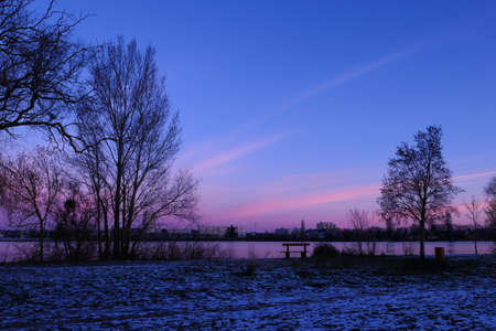 Winter scene in front of a lake. Beautiful landscape with snow on grass. Sunrise in rural scene with silhouette of tree and vegetation.