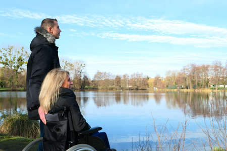 Concept of disabled person. A woman in a wheelchair with a man standing next to her, outside in the nature in front of a lake