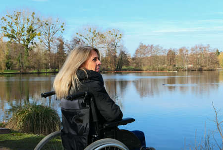 Concept of disabled person. A woman in a wheelchair outside in the nature in front of a lake.