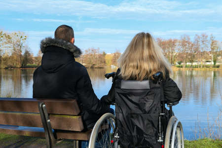 Concept of disabled person. A woman in a wheelchair outside in the nature in front of a lake. A man sitting on a bench. Background blurred voluntarily.