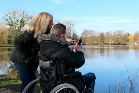 Concept of a person with a physical disability. A man in a wheelchair with a woman standing beside him. Couple using technology while looking at a smartphone. Rural scene by a lake. 版權商用圖片