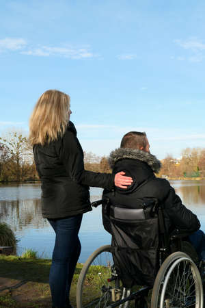 Concept of disabled person. A man in a wheelchair outside in the nature in front of a lake with blonde woman standing. Background blurred voluntarily. 版權商用圖片