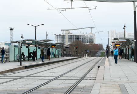 Paris, France. January 24. 2021. People waiting for the tram at an outdoor station on the side of the rails in the Bercy district. Electric and environmentally friendly public transport.
