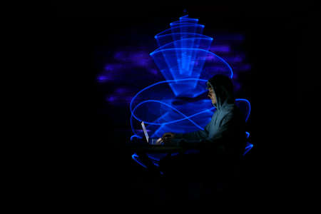Man using technology with laptop. Abstract light form in the background, made to lightpainting.