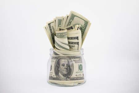 dollaro: Vaso di vetro traboccante di banconote da cento dollari ha un tracciato di ritaglio Archivio Fotografico