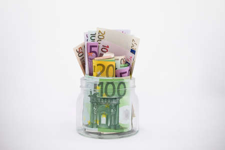 overflowing: Glass Jar Overflowing With Euro Bills has clipping path Stock Photo