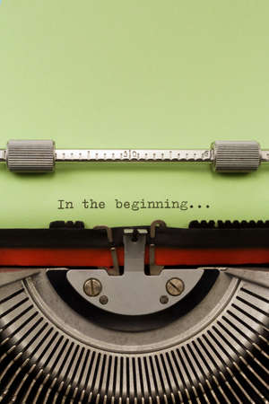 typewriter: Vintage Typewriter With Phrase In the beginning Typed on Green Paper Vertical Photograph Stock Photo