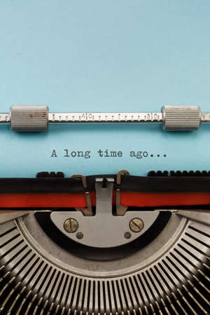 long  ago: Vintage Typewriter With Phrase A long time ago Typed on Blue Paper Vertical Photograph