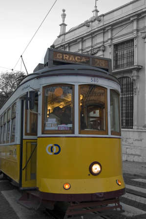 tramcar: yellow tramcar after a stop with lights on Editorial