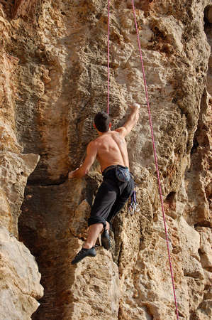 youg adult climbing over a wall of rock