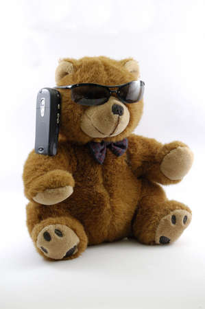 teddy bear on the phone with sun glasses isolated in a white background