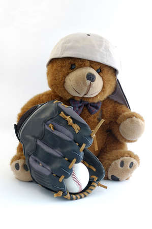 teddy bear whit a cap and glove of baseball isolated in a white background