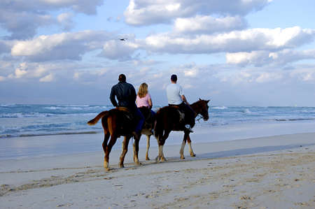 people having fun riding horses at the beach at the end of the day
