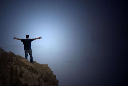 man on the top of a cliff with open arms  Standard-Bild