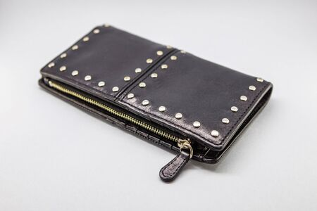 A small, feminine black purse with chrome details that can be used as a wallet. Standard-Bild