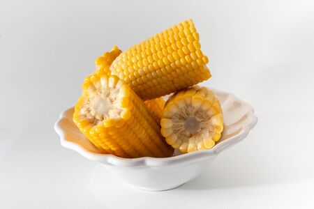 Some cooked corn very soft, hot and yellow made in the pan, seasoned with salt and butter. Served together and stacked in a white pot.