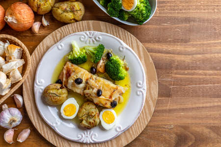 Cod loin baked in olive oil, with potatoes, broccoli, boiled egg and black olives. Typical dish of Portugal. Top view. Space for text.