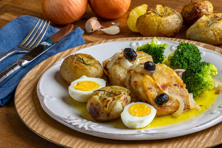 Cod loin baked in olive oil, with potatoes, broccoli, boiled egg and black olives. Typical dish of Portugal.
