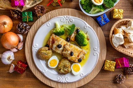 Cod loin baked in olive oil, with potatoes, broccoli, boiled egg and black olives. Typical dish of Portugal. Christmas decoration. Top view.