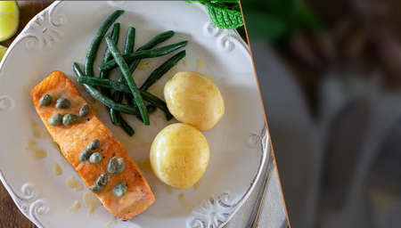 Grilled salmon fillet with caper sauce, potatoes, garlic, parsley and green beans. Selective focus. Space for text. Top view.