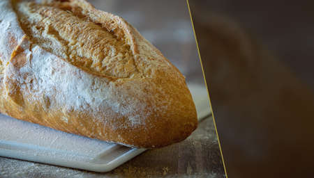 A fresh and crispy Italian bread, on a white cutting board and wheat flour. Selective focus. Space for text.