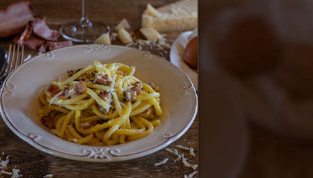 Carbonara pasta dish, typical Italian recipe with parmesan cheese, egg cream and bacon. Space for text. Selective focus.