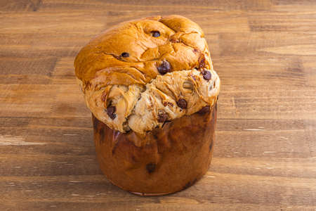 Panettone with chocolate on wooden table, traditional Italian dessert cake for Christmas.