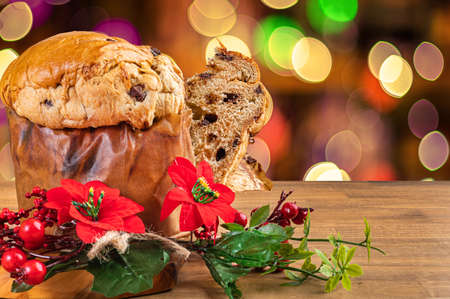 Panettone with chocolate, traditional Italian dessert cake for Christmas. Flashing lights and blurred decorations in the background. Imagens